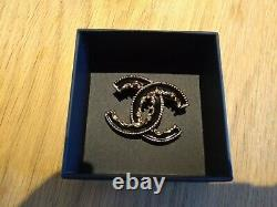 CHANEL Limited Edition! Black enamel and gold metal CC scroll brooch, In Box
